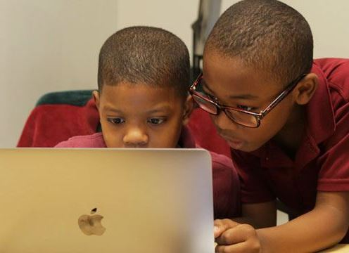 Elementary students viewing laptop computer